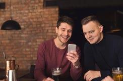 Amis appréciant la bière fraîche au bar et partageant le mobile Images libres de droits