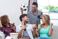 Amis appréciant la bière tout en regardant le match de football Images stock