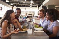 Amis appréciant la date de déjeuner dans le restaurant d'épicerie fine Photo stock