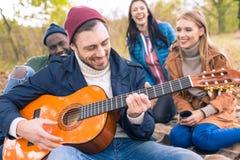 Amis appréciant la guitare en parc d'automne Photographie stock libre de droits