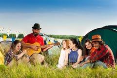 Amis appréciant la musique de la guitare sur des vacances en camping Photo libre de droits