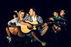 Amis appréciant la musique près du feu de camp Photos stock