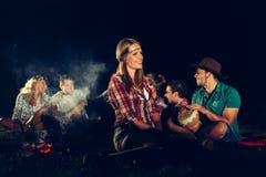 Amis appréciant la musique près du feu de camp Photographie stock