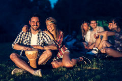 Amis appréciant la musique près du feu de camp Photo libre de droits