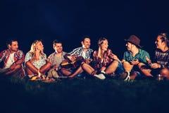 Amis appréciant la musique près du feu de camp la nuit Photos libres de droits