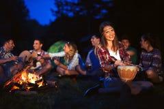 Amis appréciant la musique près du feu de camp la nuit Image libre de droits