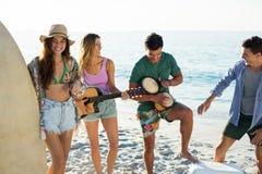 Amis appréciant la musique tout en se tenant à la plage Image stock