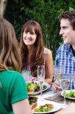 Amis appréciant la nourriture et les boissons à une réunion Images libres de droits