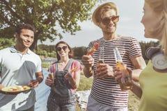 Amis appréciant le barbecue et la bière sur l'air ouvert photographie stock libre de droits