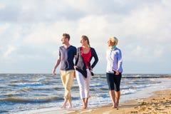 Amis appréciant le coucher du soleil à la plage d'océan Photo libre de droits