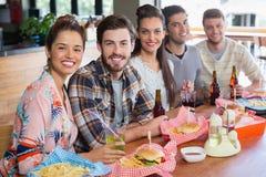 Amis appréciant le déjeuner dans le restaurant Image stock