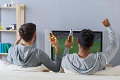Amis appréciant le football dans la TV Photos libres de droits