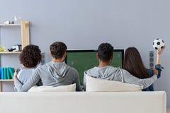 Amis appréciant le football dans la TV Images stock