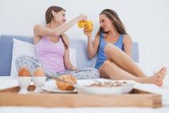 Amis appréciant le petit déjeuner dans le lit Photos stock