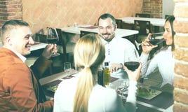 Amis appréciant le repas délicieux dans le restaurant de pays Photographie stock libre de droits