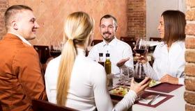 Amis appréciant le repas délicieux dans le restaurant de pays Image libre de droits