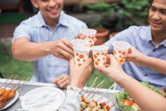 Amis appréciant le repas dans l'arrière-cour et les acclamations Photographie stock
