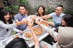 Amis appréciant le repas dans l'arrière-cour et les acclamations Photos stock