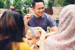 Amis appréciant le repas dans le restaurant extérieur Image libre de droits