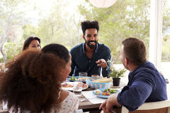 Amis appréciant le repas extérieur sur la terrasse ensemble Images stock