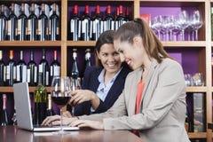 Amis appréciant le vin rouge tout en à l'aide de l'ordinateur portable au Tableau Photos stock