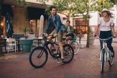 Amis appréciant montant des bicyclettes sur la rue de ville Photos stock