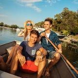 Amis appréciant sur un bateau Photos libres de droits