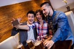 Amis appréciant tout en prenant le selfie au restaurant Photos stock