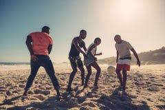 Amis appréciant un jeu du football à la plage Photographie stock libre de droits