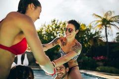 Amis appréciant un jour d'été dans la piscine Photos stock