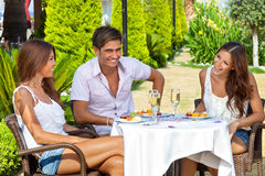 Amis appréciant un repas dans un jardin tropical Photos stock