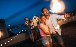 Amis appréciant une partie de dessus de toit et dansant avec des cierges magiques Photo stock