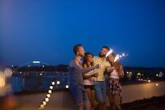 Amis appr?ciant une partie de dessus de toit et dansant avec des cierges magiques photo stock