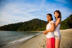 Amis asiatiques appréciant le coucher du soleil par la plage Photos stock