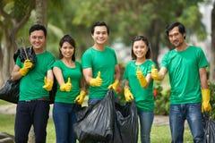 Amis asiatiques avec de pleins sacs de poubelle Photo stock