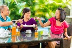 Amis asiatiques ayant le café sur le porche à la maison Photos libres de droits