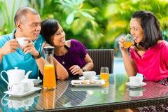 Amis asiatiques ayant le café sur le porche à la maison Image libre de droits