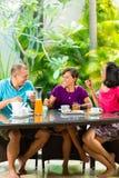 Amis asiatiques ayant le café sur le porche à la maison Photos stock