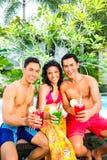 Amis asiatiques buvant des cocktails à la piscine Photos stock