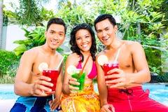 Amis asiatiques buvant des cocktails à la piscine Image libre de droits