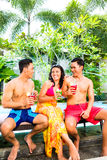 Amis asiatiques buvant des cocktails à la piscine Photo libre de droits