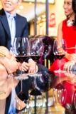 Amis asiatiques buvant du vin dans la barre Photos libres de droits