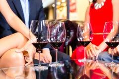 Amis asiatiques buvant du vin dans la barre Photo libre de droits