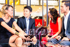 Amis asiatiques buvant du vin dans la barre Photo stock