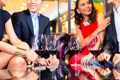 Amis asiatiques buvant du vin dans la barre Photos stock