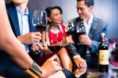 Amis asiatiques buvant du vin dans la barre Image libre de droits