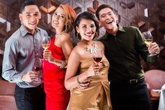 Amis asiatiques buvant du vin dans la barre Image stock