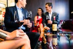 Amis asiatiques buvant du vin dans la barre Images libres de droits