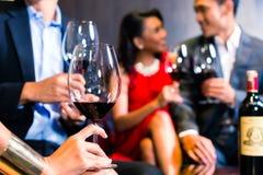 Amis asiatiques buvant du vin dans la barre Photographie stock libre de droits