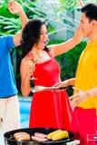 Amis asiatiques célébrant le BBQ de réception au bord de la piscine Image stock